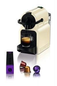 foto de cafetera sirviendo una taza de café y capsulas sueltas alrededor